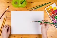 Kids hand holding a paintbrush on blank page, top view Royalty Free Stock Images