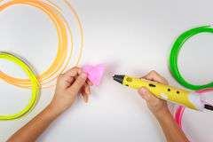 Kids hand holding yellow 3D printing pen with filaments and makes heart on white background. Top view. Copy space for Stock Photo