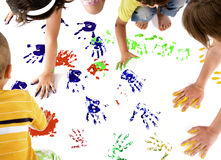 Kids hand prints. Kids making colourful hand prints on white copy space stock photography