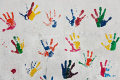 Kids hand prints. Multiple colored hand prints on white wall background stock image