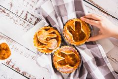 Kids hand taking a tartlets sprinkled with powdered sugar with peach jam stock photo