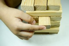 Kids hand playing with woodblock. Kids hand touching and playing with wood blocks royalty free stock image
