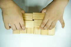 Kids hand playing with woodblock. Kids hand touching and playing with wood blocks stock photos
