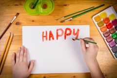 Kids hand writing a greetings with paintbrush at the table Royalty Free Stock Images