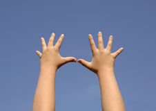 Kids hands. Of a caucasian white boy up to the blue sky background stock photography