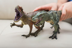 Kids hands catching a brown Carcharodontosaurus and a green tyrannosaurus toy Royalty Free Stock Photography