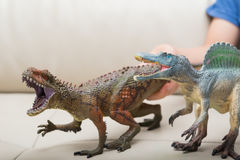 Kids hands catching a brown Carcharodontosaurus and a grey Spinosaurus toy on a sofa Stock Photos