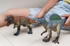 Kids hands catching a brown tyrannosaurusaurus and a grey Spinosaurus toy on a sofa Royalty Free Stock Images