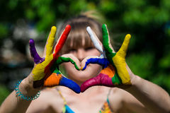 Kids hands in color paints make a heart shape, focus on hands stock photos