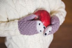 Kids hands in cozy mittens holding red apple Royalty Free Stock Images