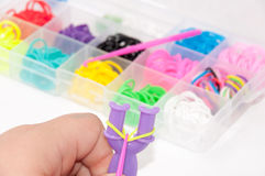 Kids hands creating bracelet with rubber bands and box in the ba Royalty Free Stock Photo