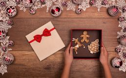 Kids hands opening christmas gift with gingerbread cookies Royalty Free Stock Image
