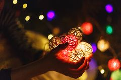 Kids hands hold a ball garland for Christmas or New year at home on lights background. New year and Christmas celebration, stock image