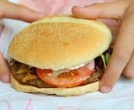 Kids hands hold hamburger close up photo. Hamburger from fast food restaurant Stock Photo