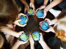 Kids hands holding cupping globe balls together Stock Image