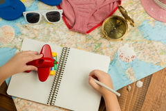 Kids hands holding pen, writing notes, holding red plane. Traveling theme items on the table. Summer vacation with child. Top view Stock Photo