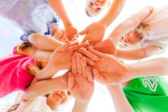 Kids hands together in circle laying one on another royalty free stock photo