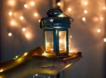 Kids hands holds Christmas lantern in hands on lights bokeh background. royalty free stock photo