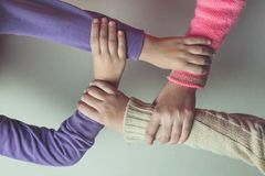 Kids hands join together on the table. stock photos