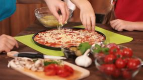 Kids hands making a pizza putting on the grated cheese stock video