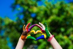 Kids hands painted in bright colors make a heart shape on summer nature background stock photos