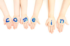 Kids hands painted with welcome come in sign. On white Royalty Free Stock Photos