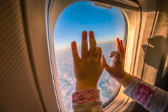 Kids hands on the plane window. Girls hands on the plane window during flight above the clouds royalty free stock photo