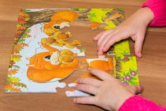 kids hands playing with puzzle, education concept. stock photos