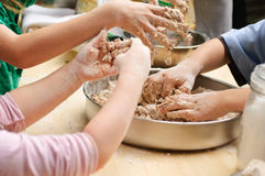 Kids hands preparing dough. Kids hands preparing bread dough Royalty Free Stock Image