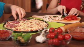 Kids hands putting the salami slices on pizza stock footage