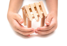 Kids hands surrounding a house model Stock Photo