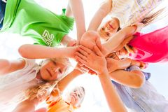 Kids hands together in circle laying one on another stock photos
