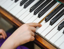 Kids hands on a white piano key Stock Photo