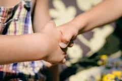 Kids handshake closeup on sunny outdoors background Stock Photos