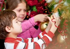 Kids hanging Christmas ball Stock Photography