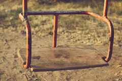 Kids hanging swing rusty metal with wooden seat outdoors Stock Images