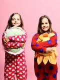 Kids with happy faces hold green and yellow sun pillows. Childhood and friendship concept. Girls with loose hair hug their pillows. Friends in pink polka stock photography
