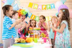 Kids are happy after they have blowed candles out on birthday party. Childs are happy after they have blowed candles out on birthday party. Kids with clown clap royalty free stock photos
