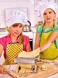 Kids in hat making homemade pasta at kitchen. Stock Image