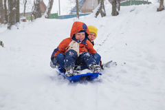 Kids have fun sledding with snow slides.  Royalty Free Stock Photography