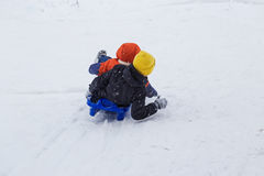Kids have fun sledding with snow slides Royalty Free Stock Photography