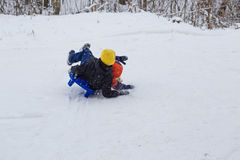 Kids have fun sledding with snow slides Stock Images
