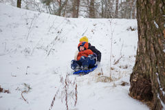 Kids have fun sledding with snow slides Stock Photography