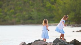 Kids have a lot of fun at tropical beach playing together. Little girls having fun at tropical beach playing together at shallow water. Adorable little sisters stock footage