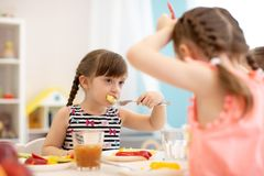 Kids have lunch in daycare, kindergarten or home stock photography