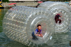 Pengzhou, China: Kids in Inflated Water Wheels Stock Photo