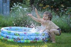 Kids having fun. Kids splashing in water on a hot day Royalty Free Stock Image
