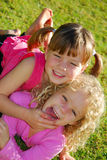 Kids having fun. Outdoor portrait of two caucasian girls with funny facial expression having great fun Stock Image