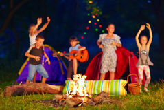 Kids having fun around campfire. focus on fire royalty free stock photo