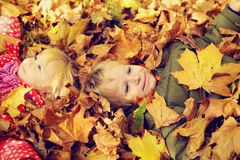 Kids having fun in autumn fall leaves Stock Image